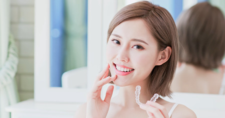 close up of woman smile happily and take invisible brace