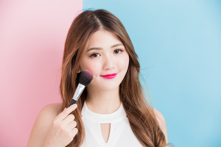 pretty girl take makeup brush in white dress isolated on a pink and blue background 写真素材
