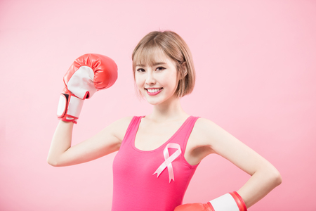 woman wear pink ribbon and hold boxing gloves with prevention breast cancer concept Reklamní fotografie