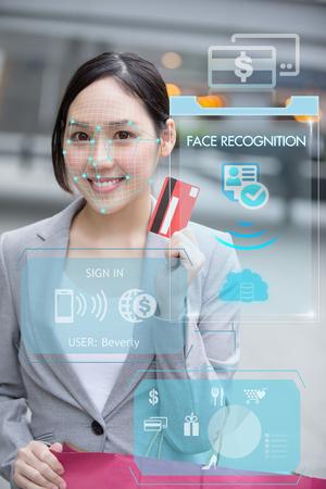 Asiatische Geschäftsfrau, die Kreditkarte zur Zahlung mit Gesichtserkennung verwendet