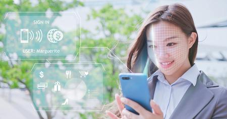 Mujer de negocios asiática está comprando en teléfonos inteligentes con reconocimiento facial de escaneo. Foto de archivo