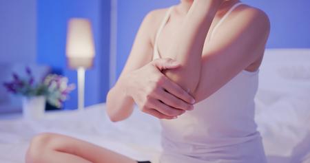 Schönheit Frau tragen Creme mit Ellbogen auf das Bett in der Nacht