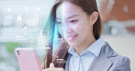 Une femme d'affaires fait des achats sur un téléphone intelligent avec la reconnaissance faciale par balayage. Banque d'images