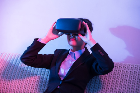 businesswoman sit on sofa and wear virtual reality headset at home