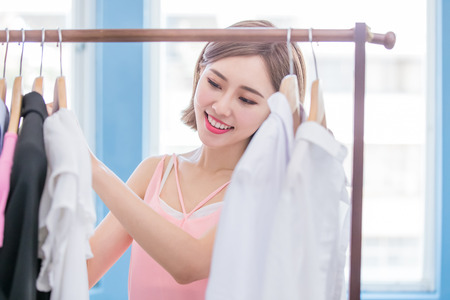 young woman choosing clothes on a rack in a showroom Banque d'images