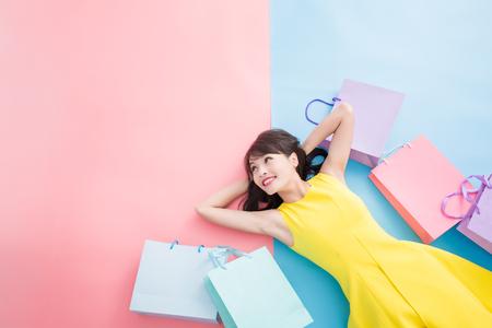 Mujer toma la bolsa de compras felizmente y mira copia espacio sobre el fondo azul y rosa Foto de archivo