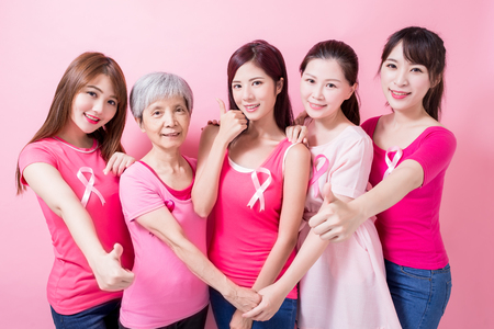 women with breast cancer prevention and show thumb up on the pink background