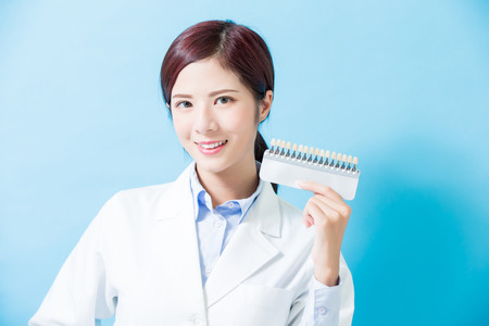 dentist take tooth whitening tool on the blue background