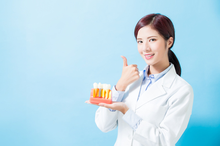 woman dentist take implant tooth and thumb up on the blue background Imagens