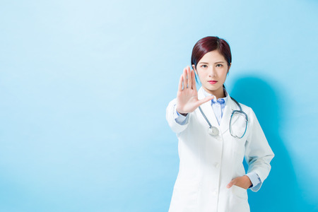 woman doctor show stop gesture on the blue background 스톡 콘텐츠