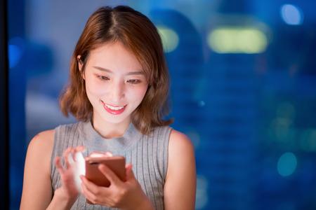 mujer usa el teléfono felizmente en casa por la noche Foto de archivo
