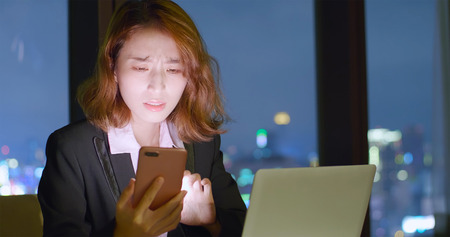 business woman feel tired use phone and notebook work at night