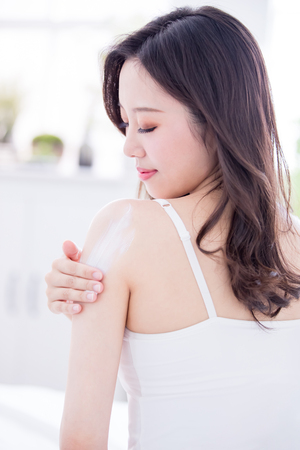 Young skin care woman applying body lotion on arm and shoulder at home Stockfoto - 110795201