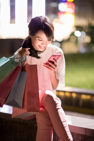 woman use phone happily and take shopping bag Stock Photo
