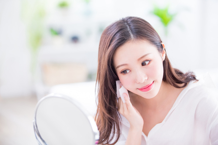 Glimlach vrouw verwijder make-up door Cleansing Cotton en kijk thuis in de spiegel