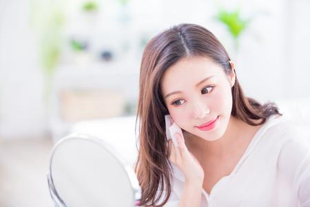 Lächelnde Frau entfernt Make-up durch Cleansing Cotton und schaue im Spiegel zu Hause