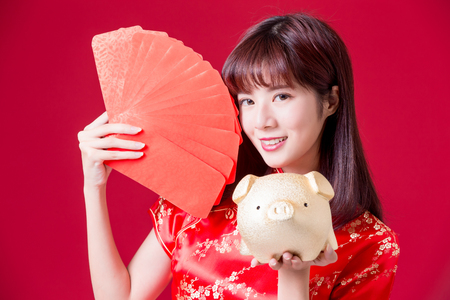 beauty woman show golden pig bank and red envelope in chinese new year
