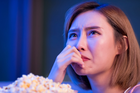 Young woman cry while watching a tragedy movie at night 版權商用圖片