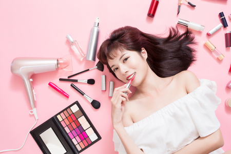 Young beautiful woman use lipstick with her cosmetic makeup tools - she is lying on the pink floor