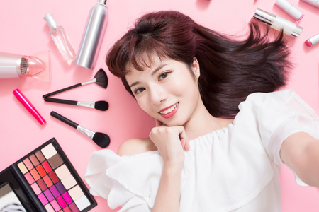 Young beautiful woman take a selfie with her cosmetic makeup tools - she is lying on the pink floor