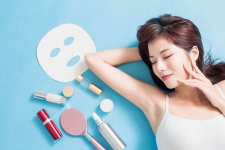 Beauty woman relax closed eye and touch face with her skin care product - she is lying on the blue floor Archivio Fotografico