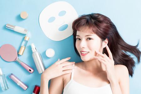 Beauté femme sourire avec son produit de soin de la peau - elle est allongée sur le sol bleu