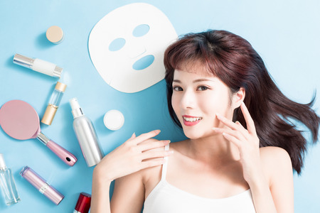 Beauty woman smile with her skin care product - she is lying on the blue floor