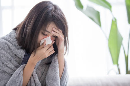 woman sick and sneeze with tissue paper at home
