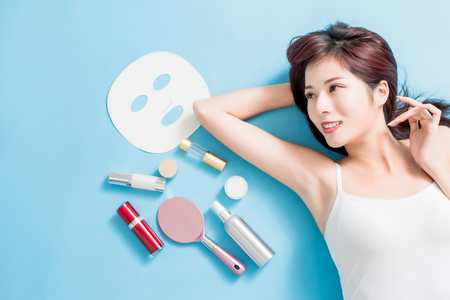 Beauty woman look somewhere with her skin care product - she is lying on the blue floor