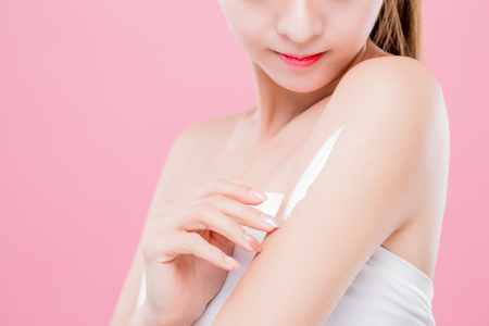Schönheitsfrau benutzt Creme mit dem Arm lokalisiert auf rosa Hintergrund