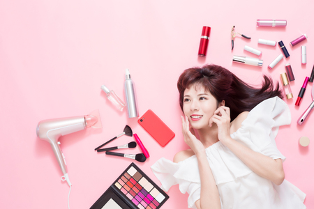 Young beautiful woman smile and look copy space with her cosmetic makeup tools - she is lying on the pink floor