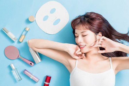 Beauty woman relax closed eye with her skin care product - she is lying on the blue floor Stockfoto