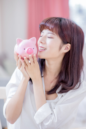 Happy woman save money to her pink piggy bank and kiss it at home