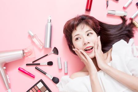 Młoda piękna kobieta uśmiecha się i patrzy gdzieś swoimi kosmetykami do makijażu - leży na różowej podłodze Zdjęcie Seryjne