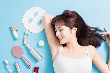 Beauty woman relax closed eye with her skin care product - she is lying on the blue floor Imagens