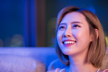 Young woman watching movie happily at night