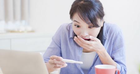 opgewonden vrouw kijkt vrolijk naar de zwangerschapstest en voelt zich verrast