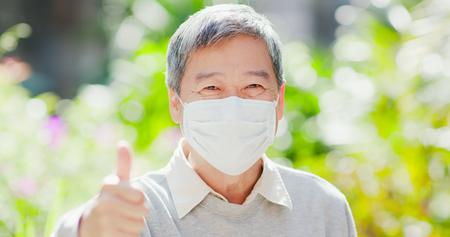 de glimlach van de oude man laat de duim zien en draagt een masker met een groene achtergrond van de natuur Stockfoto