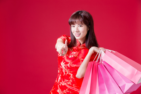 beauty woman wear cheongsam pointing to you and hold shopping bags in chinese new year Banco de Imagens