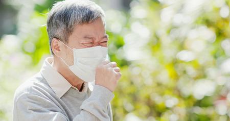 oude man draagt een masker en hoest buiten
