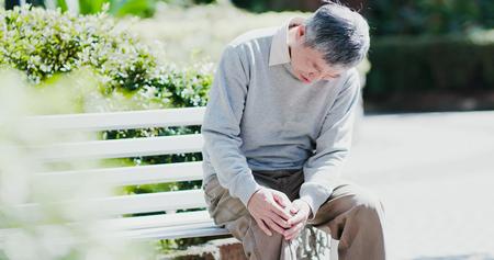 oude man met een knieprobleem in het park Stockfoto