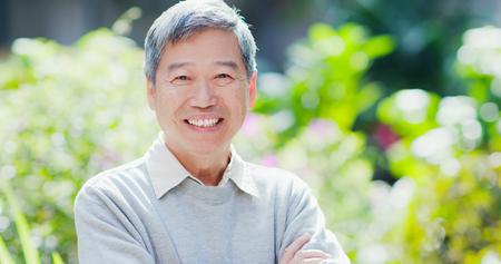 alter mann lächelt dir mit naturgrünem hintergrund zu