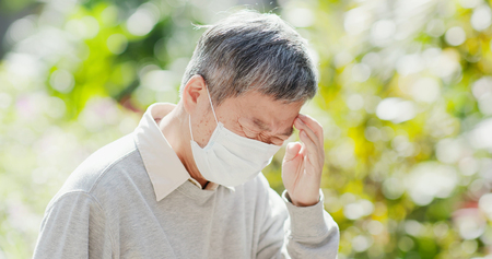 old man wear mask and feel headache outdoor Stock Photo