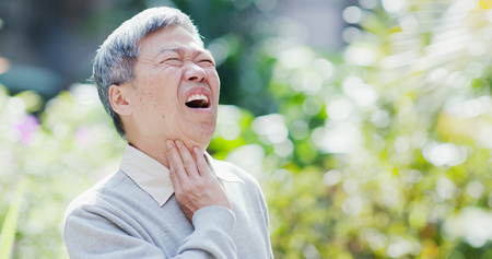 old man get a cold and feel throat pain outdoor or symptom of esophageal cancer Zdjęcie Seryjne