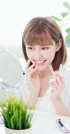 Beauty woman look her beautiful teeth in the mirror happily after take off the invisible brace 免版税图像