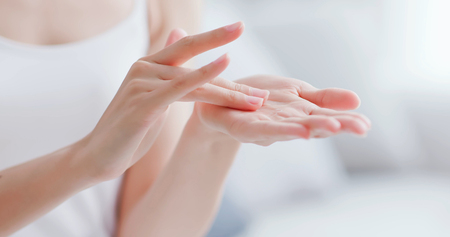 beautiful woman apply moisturizer into her hand at home