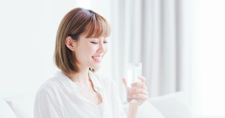 Beauty woman drink water and feel happily at home 스톡 콘텐츠