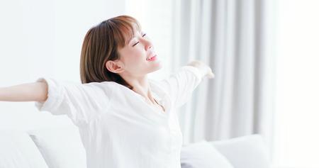 junge Frau fühlt sich unbeschwert und streckt den Arm, um zu Hause tief durchzuatmen