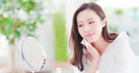 Sonrisa mujer asiática quitar el maquillaje con algodón limpiador y mirar espejo en casa Foto de archivo