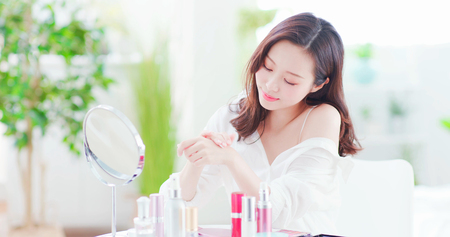 Giovane donna asiatica di bellezza che applica la crema per le mani a casa